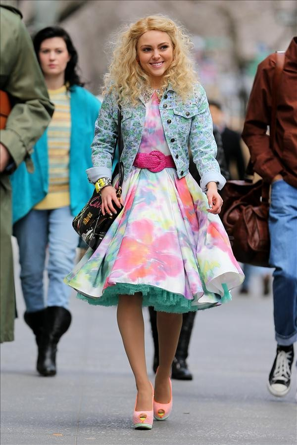 Actress Annasophia Robb, wearing a floral print dress with orange and yellow high heels, walks down Fifth Avenue filming The Carrie Diaries in New York City